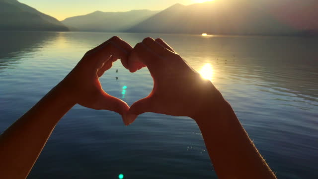 Woman's Hands Form Heart Shape Against Sun in Sunset and Alpine Lake with Mountain