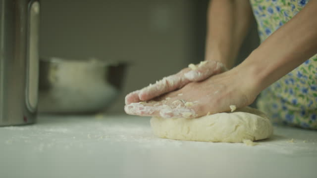 a woman's hands form pastry dough into a flat round on a white table - dough stock videos & royalty-free footage