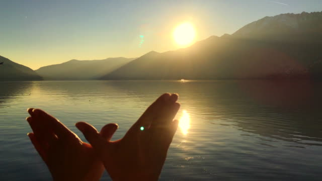 Woman's Hands Forms Bird Wings Against Sun in Sunset on Alpine Lake with Mountain