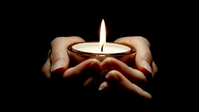 Woman's hands holding a burning candle that gets blown out