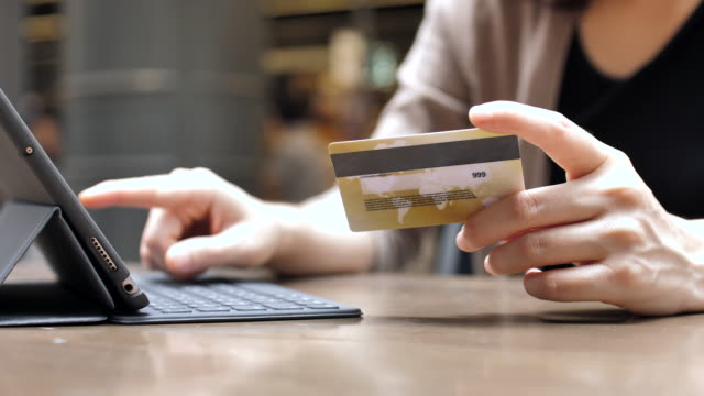 woman's hands holding a credit card and buying online with a digital tablet, slow motion - acquisto con carta di credito video stock e b–roll
