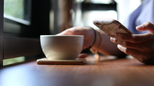 Frauenhand holding Tablet in Coffee-Shop