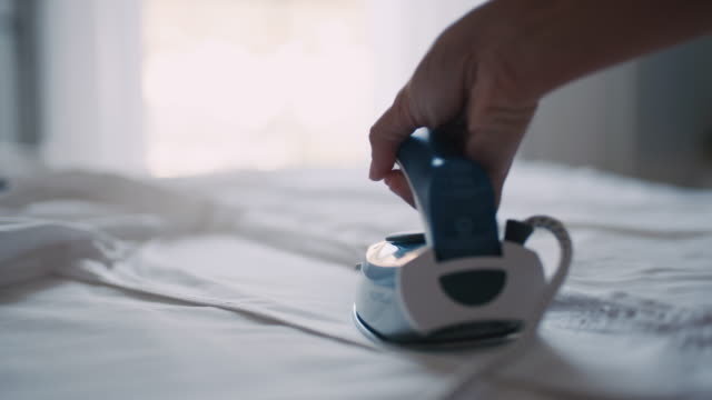 slo mo woman's hands ironing a shirt - iron appliance stock videos & royalty-free footage