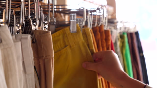 cu womans hands looking at pants on rack in clothing boutique - hanging stock videos & royalty-free footage
