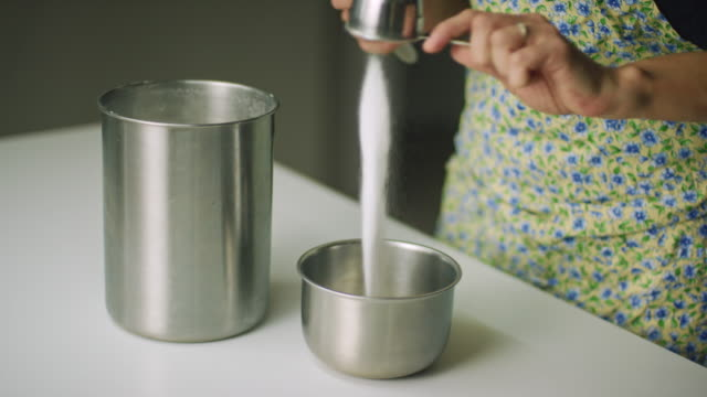 A Woman's Hands Measure White Sugar from a Canister with a Metal Measuring Cup and Pour it into a Small Metal Mixing Bowl