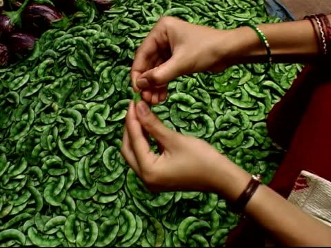 Woman's hands opening pea pod over heap of pea pods at outdoor market / Bangalore, Karnataka, India