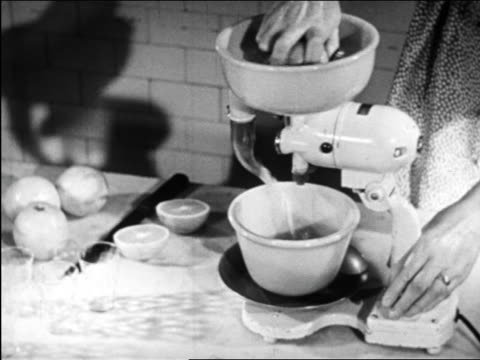 b/w 1948 woman's hands operating electric juicer / industrial - food processor stock videos and b-roll footage