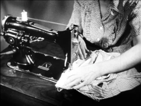 B/W 1948 woman's hands operating electric sewing machine / industrial