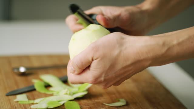 女性の手は野菜の皮むき器と青リンゴの皮をむくし、木製まな板の上の薄いスライスにカット - 切る点の映像素材/bロール