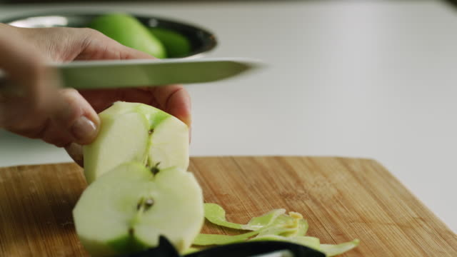 a woman's hands peel a green apple with a vegetable peeler, cut the apple in half, core it, and slice it with a kitchen knife on a wooden cutting board  in real time - peeling food stock videos & royalty-free footage