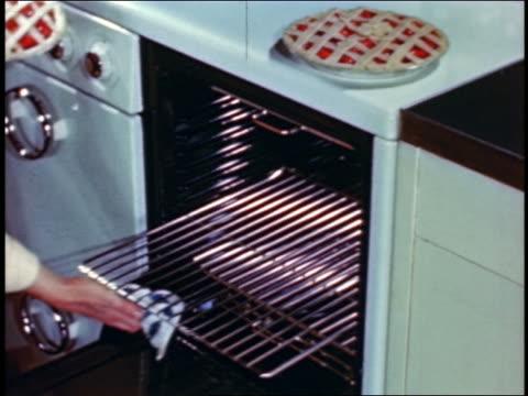 vídeos y material grabado en eventos de stock de 1946 woman's hands putting 2 pies onto oven rack + pushing rack into oven + closing oven door - pastel dulce