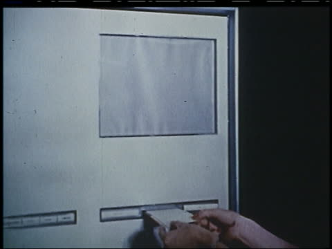 vidéos et rushes de 1956 woman's hands putting card into slot, photo of cake appears on screen in futuristic kitchen - 1956