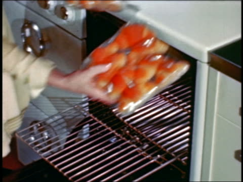 1946 woman's hands putting packets of rolls onto oven rack + pushing rack into oven