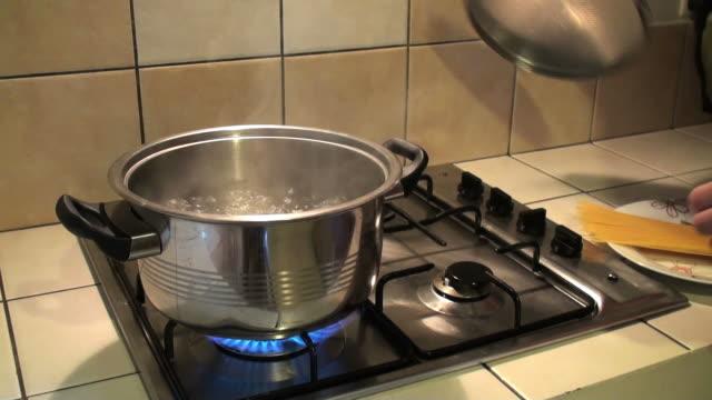 Femme mains putting spaghetti dans de l'eau bouillante