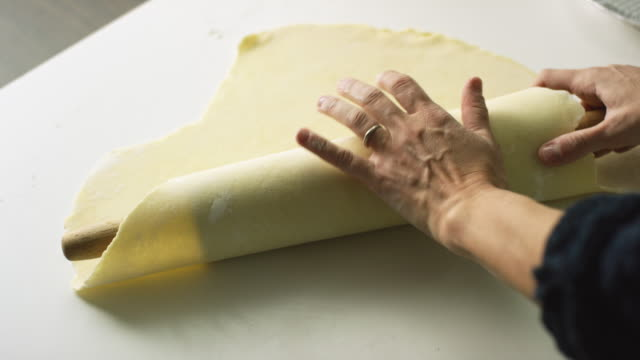 vídeos de stock e filmes b-roll de a woman's hands roll a large, flat piece of pastry dough over a wooden rolling pin, pick it up, and roll it on to a metal pie tin - pie humano