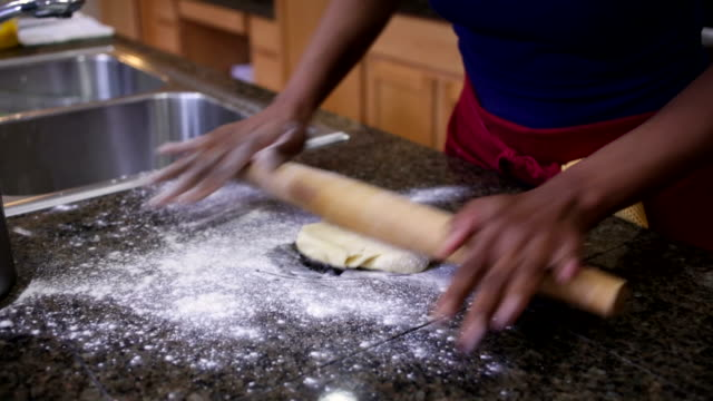 woman's hands rolling out dough on counter with rolling pin - rolling pin stock videos & royalty-free footage