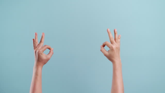 woman's hands showing her fingers making ok sign on copy space and moving sign language isolated over blue background - hand sign stock videos & royalty-free footage