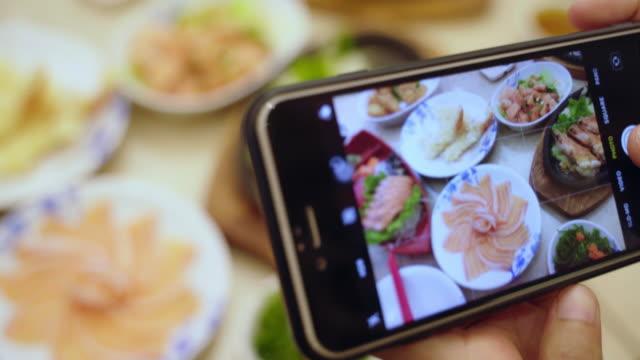 vídeos y material grabado en eventos de stock de manos de mujer 4k tomando foto de sashimi fresco, salmón comida japonesa con teléfono inteligente a la red social. - huevo comida básica