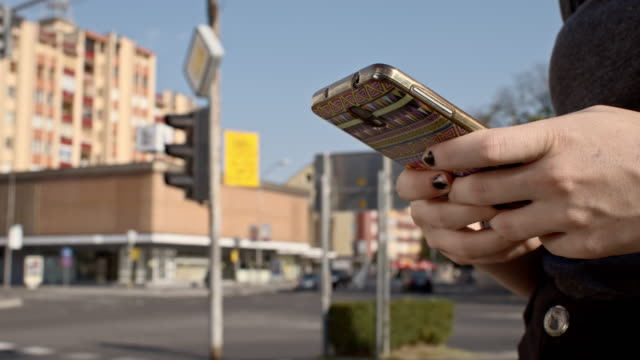 Woman's hands using a smartphone in the city