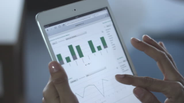vídeos y material grabado en eventos de stock de woman´s hands using tablet with statistics - diagrama