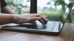 A woman's hands working and typing on laptop keyboard on wooden table and closing when finish using it