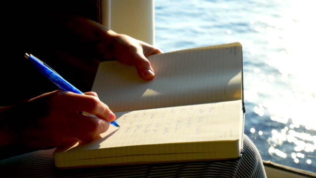 woman's hands write on the agenda during a ship trip - author stock videos & royalty-free footage