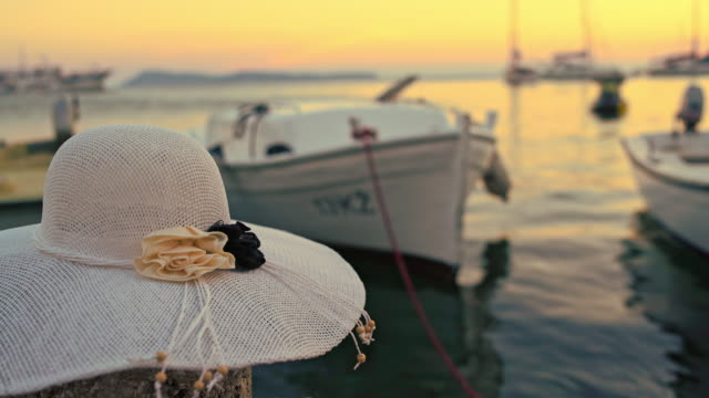 DS Woman's hat on the pier at sunset