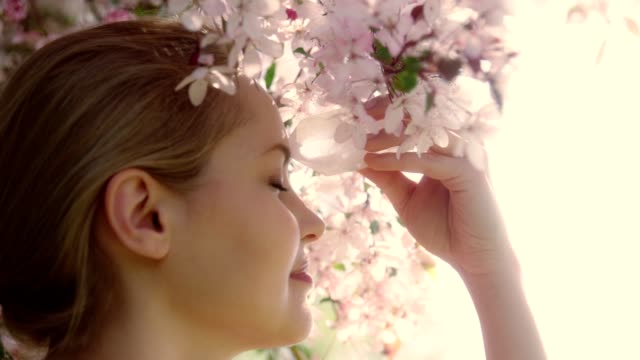 Woman's head with a healing crystal against falling petals of Cherry Blossom Tree