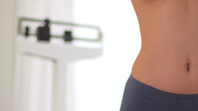 woman's hip with scale in background after losing weight - hüfte stock-videos und b-roll-filmmaterial