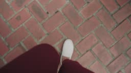 POV of woman's hipster foot while walking with brick abstract floor
