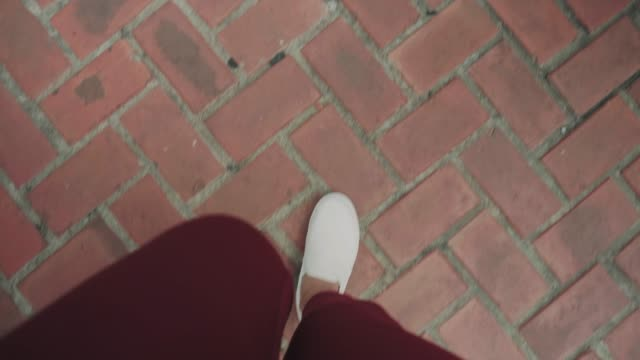 pov of woman's hipster foot while walking with brick abstract floor - personal perspective stock videos & royalty-free footage