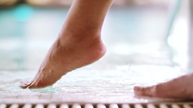 vídeos y material grabado en eventos de stock de pierna de la mujer pruebas de agua en piscina - albornoz
