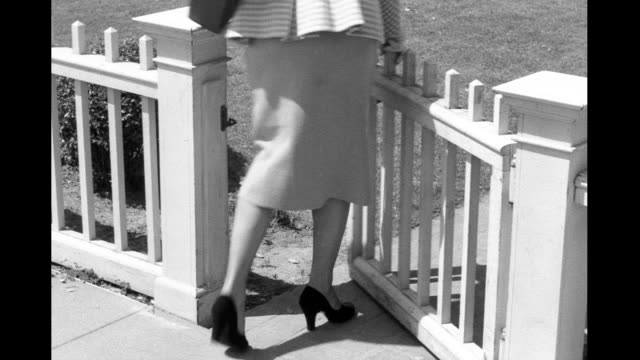 woman's legs as she walks along sidewalk next to white picket fence / goes through wooden gate them jumps back over gate with dog in pursuit woman... - picket fence stock videos & royalty-free footage