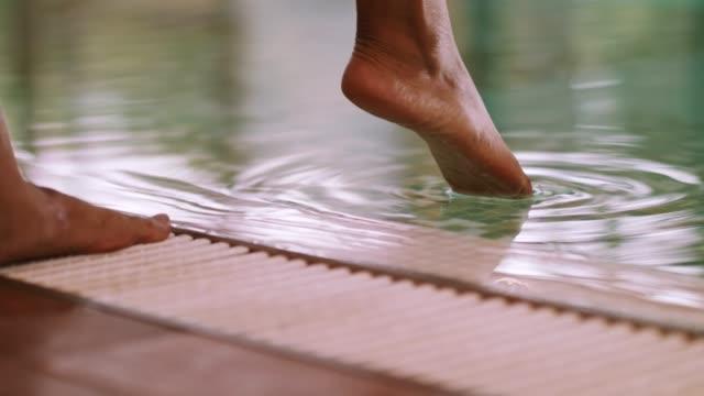 vídeos y material grabado en eventos de stock de piernas de la mujer por sentir la temperatura del agua de la piscina - en el borde