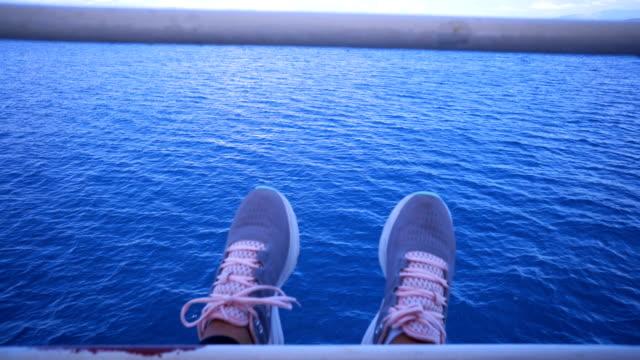 Woman's legs dangling from boat deck