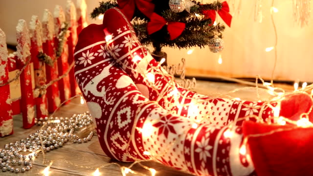 Woman's legs in seasonal winter socks by th Christmas decoration