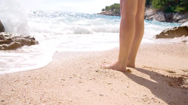 SLO MO pernas da Mulher na praia