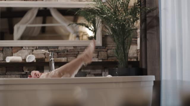 slo mo woman's legs splashing in a bubble bath - bubble bath stock videos & royalty-free footage