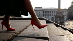 Woman's legs stepping down on stairway in city