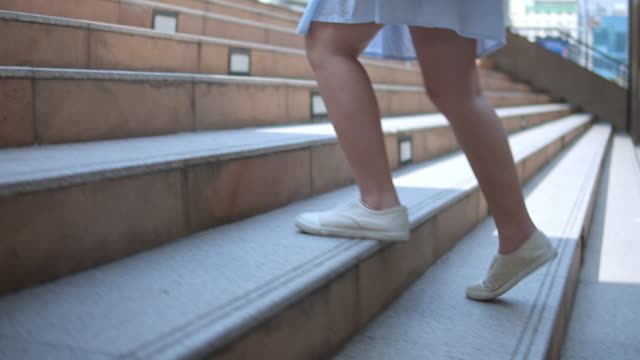 vídeos de stock e filmes b-roll de woman's legs stepping up on stairway in the city,slow motion - passos