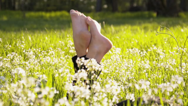 stockvideo's en b-roll-footage met dl woman's legs sticking out of the grass - op de buik liggen