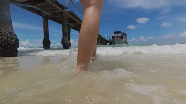 SLOW MOTION CLOSEUP: Woman's legs walking on a sandy beach