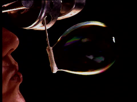 Woman's mouth blows soap bubble from bubble making device which floats around against black background