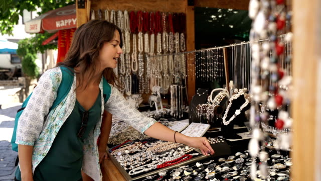 woman's stuff-buying jewelry on vacation - souvenir stock videos & royalty-free footage