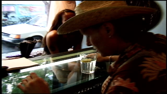 cu womans tribal tattoo as she talks to man in cowboy hat in nyc - tattoo stock videos and b-roll footage