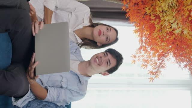 stockvideo's en b-roll-footage met vrouwen en man van aziatische afkomst, in de leeftijd van 20-30, dragen casual kleding en zijn met behulp van computer thuis, nieuwe normale kantoor levensstijl na coronavirus heropenen, - adn