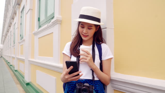 frauen im alter von 20-30 jahren, die neben einer wand stehen und ein glas heißen kakao und ein handy-smartphone halten, um einen termin zu vereinbaren, um standorte mit freunden zu teilen. - photo messaging stock-videos und b-roll-filmmaterial