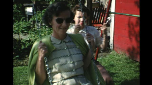 vidéos et rushes de 1953 montage women and boy (2-3) on swings, toronto, ontario, canada - 1953