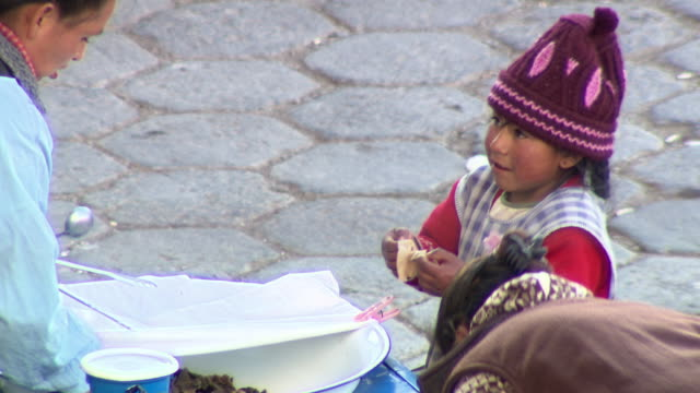 stockvideo's en b-roll-footage met cu of women and child setting up food cart, child tastes some and smiles, cochabamba, bolivia - bolivia