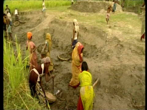women and children building mud platforms to raise homes above flood waters bangladesh; 2006 - erektion stock-videos und b-roll-filmmaterial